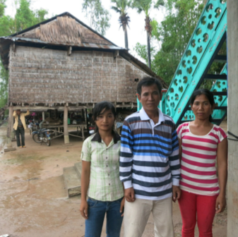 Theara and his two daughters in front of their house