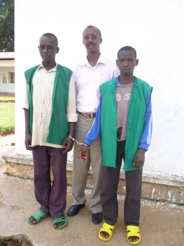 Janvier Ncamatwi (in the middle) with Eric Nimbona (on the right), a child accused of rape with another defendant. The two prisoners are attached by handcuffs.
