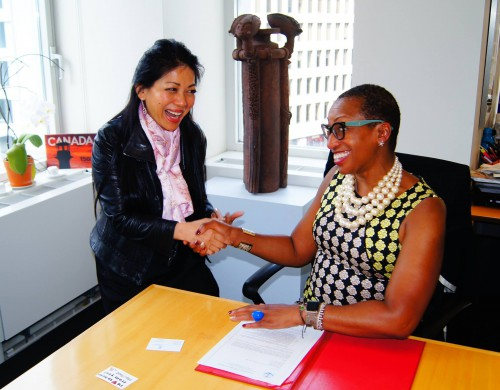 Karen Tse and Sandie Okoro shaking hands after the signing ceremony.